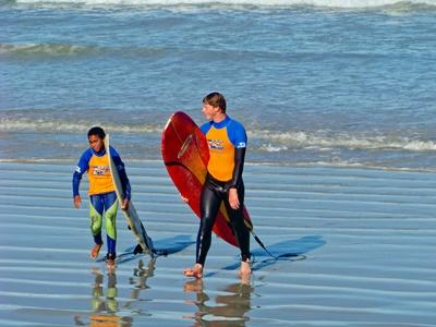 A Male volunteer walks with a boy in a surf project in South Africa