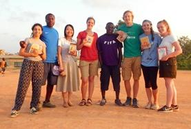 Volunteers pose with books on a language course add-on placement in Ghana