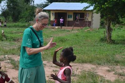 A volunteer high fives a child in Ghana