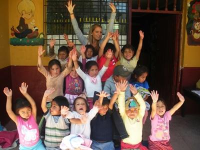 Projects Abroad volunteer posing for a photo with children in Peru