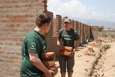 Volunteers carry bricks on Building placement