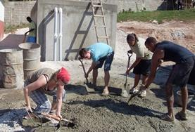 Volunteers shovel cement as part of their building efforts