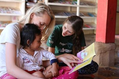 Volunteers read to a child in Cambodia, Asia