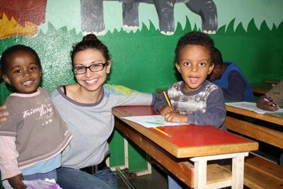 Care volunteer helps children with drawing and colouring-in, Ethiopia