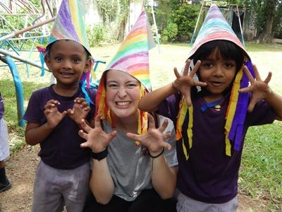 Project Abroad volunteer plays dress up with a young boy and girl at a Care placement