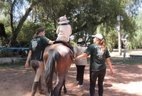 A child rides a horse being led by volunteers on an Equine Therapy Project in Bolvia