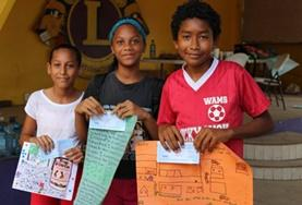 Children pose with posters at a Care Project in Belize