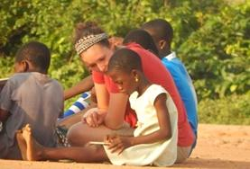 A Care volunteer sits and interacts with children on a placement in Ghana