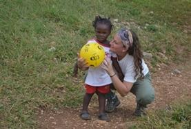 A volunteer poses with a child who holds a ball