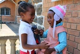 Two children laugh together at one of our childcare placements in Madagascar.