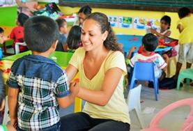 A Care volunteer interacts with children at a placement in the Philippines