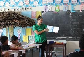 A volunteer working with children reads an English book to her class in Samoa.