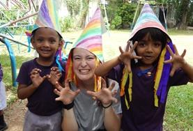 A childcare volunteer in Sri Lanka runs a creative arts and crafts lesson, teaching children to make colourful hats.