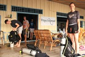 Diving & Marine Conservation volunteers prepare for a survey dive in Cambodia by setting up their scuba equipment.