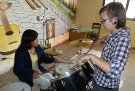 A volunteer and student interacts with muscial instruments