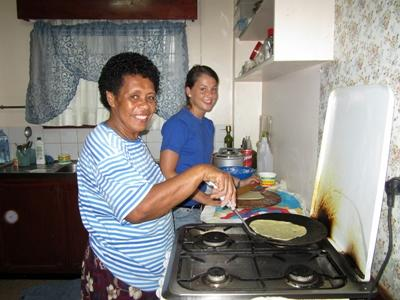 A volunteer helps her host mother cook dinner
