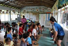 A group of volunteers spends time with children in a local village in Samoa during their cultural immersion project.
