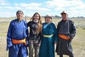 A volunteer poses with a group of Nomads at a placement in Mongolia