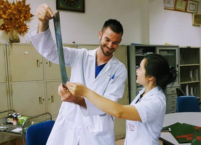 Medical volunteer Brandon Gepford at National Hospital of Traditional Medicine looking at an x-ray with staff
