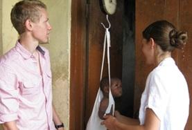 A midwifery student assists with weighing a baby at his volunteer elective placement in a Ghanaian health clinic.