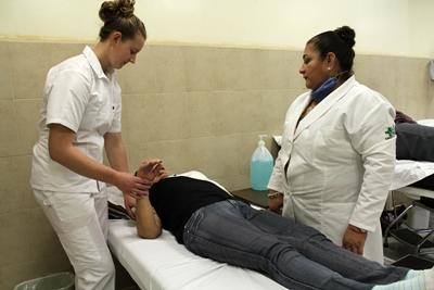A Nursing student volunteer and local doctor examine patient