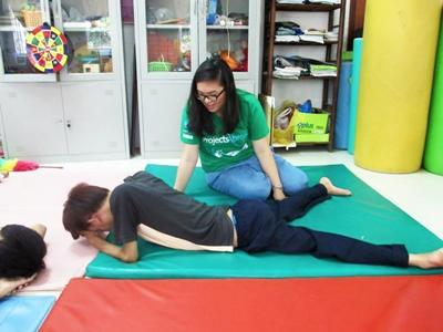 Projects Abroad Care volunteer, Cindy Do from the USA, helps with physiotherapy work with Agent Orange Victims at the Thuy An Rehab Centre