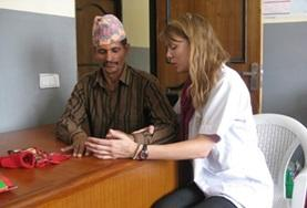 A volunteer on her Physiotherapy Elective works on stretches to improve fine motor coordination for a local man in Nepal.