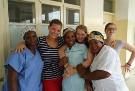 An intern doing her Midwifery Elective in a developing country holds a newborn baby.