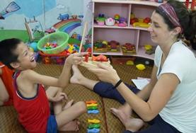 An intern doing her Occupational Therapy Elective in a developing country works on a painting activity with a disabled child.