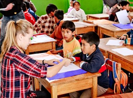 A female volunteer helping children in a classroom in Peru, South America