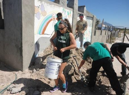 Female volunteer carrying sand at the building site in South Africa