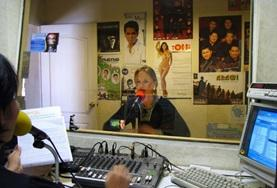 A Journalism volunteer participates on a radio braodcast
