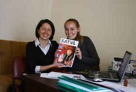 A local journalist and a Journalism intern in Romania hold the magazine that they have been working on together.