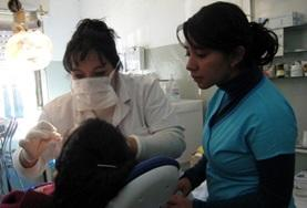 A destist examines a patient's teeth and gums while an assistant observes