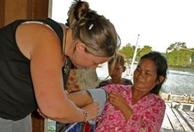 A Medicine intern measures a local woman's blood pressure at her volunteer Medical placement in Cambodia.