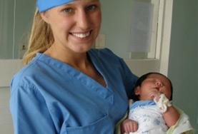 A Midwifery volunteer holds a newborn at her placement in Mongolia