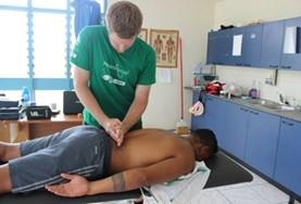 A Physiotherapy intern treats a rugby player in Samoa who has injured himself during a match.