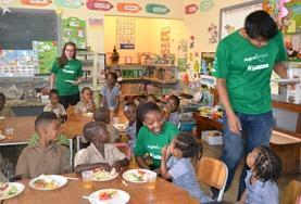 Nutrition volunteers provide nutritious meals to children at a local school to promote healthy eating.