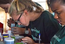 Pharmacy interns sort through medication and help with distributing it to members of a local community during a volunteer outreach.