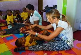A Physiotherapy volunteer does light stretches with a boy at a care centre as part of our Medical internship in Tanzania.
