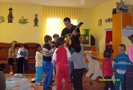 A volunteer Art Therapist plays music for children at a placement in Romania