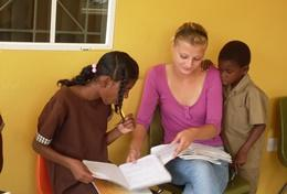 A Social Work volunteer has a discussion with local children