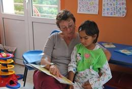 A volunteer Social Worker reads to a child at a placement in Romania