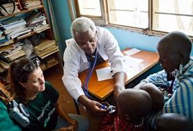 A volunteer and doctor inspect children