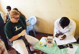 A volunteer and local nurse make notes