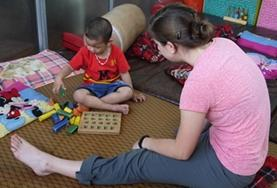 A qualified Occupational Therapist volunteer in Vietnam assesses a disabled child using a game that requires fine motor skills.