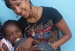 A Physiotherapy volunteer poses with a child