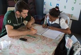 A professional Basic Skills Teacher volunteering in Belize conducts a one-on-one literacy lesson with a school child.
