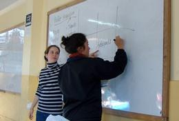 Volunteer Maths Teachers write on a whiteboard at a placement in Peru