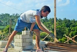 A Building volunteer assists in construction work at a placement in the Philippines